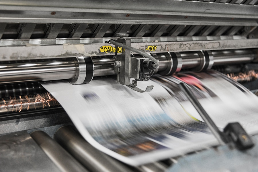 image of a printing press quickly printing pages
